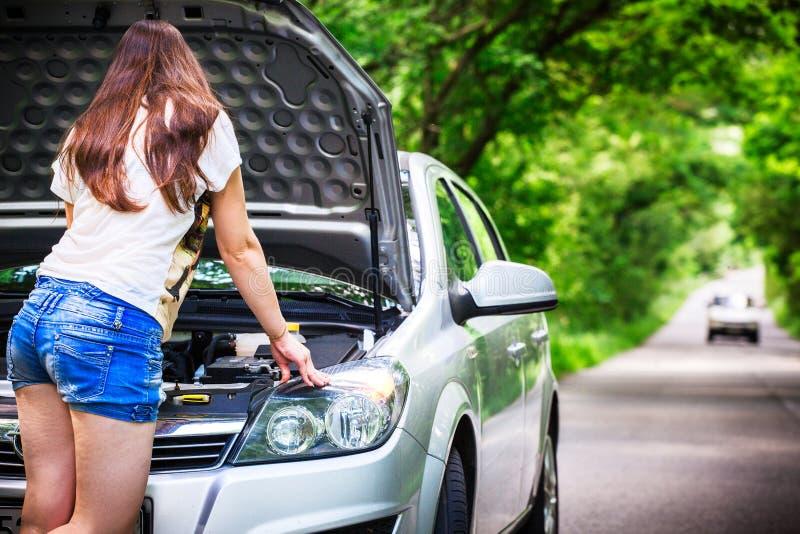 La jeune femme de brune se tient près d'une voiture argentée sur le bord de la route Femme près de la voiture avec le capot ouver photo libre de droits
