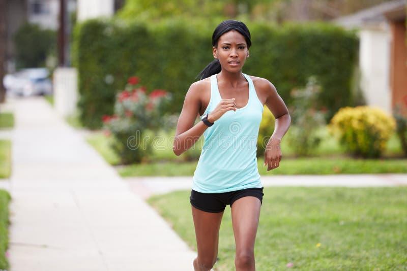 La jeune femme de couleur dans les sports vêtx le fonctionnement dans la rue photo stock