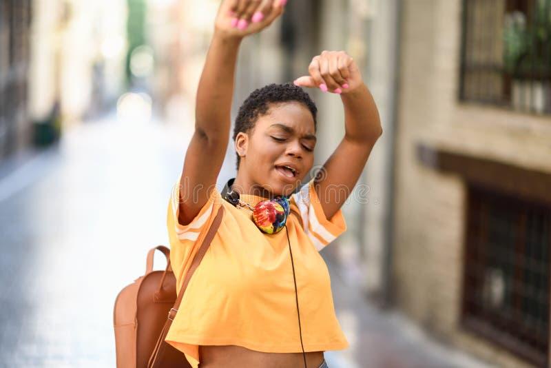 La jeune femme de couleur danse sur la rue en été Fille seul se d?pla?ant images libres de droits