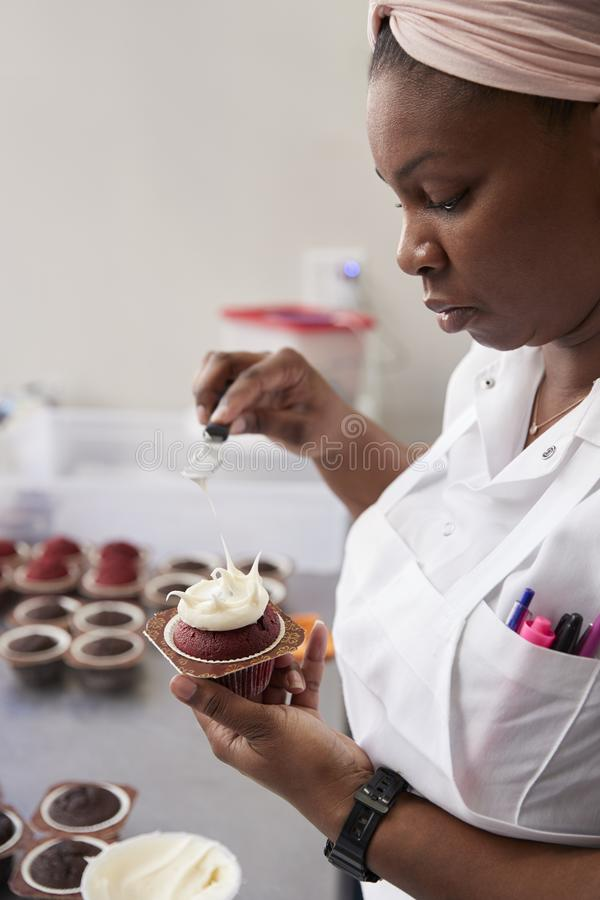 La jeune femme de couleur préparant la nourriture dans une boulangerie, se ferment  image stock
