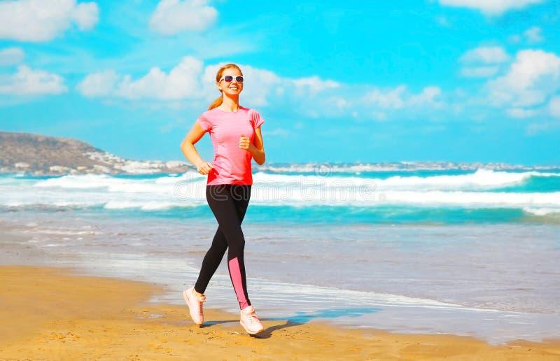 La jeune femme de forme physique est été courant le long de la plage près photo stock