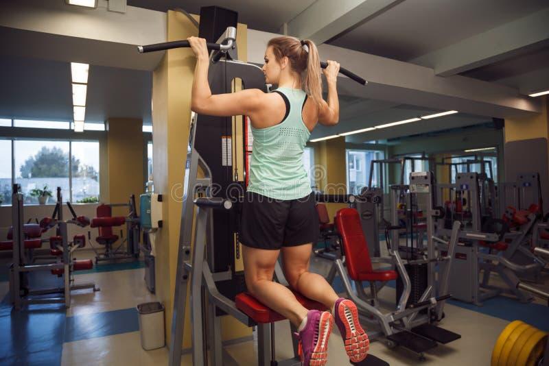 La jeune femme de forme physique exécutent l'exercice avec l'exercice-machine en Th image stock