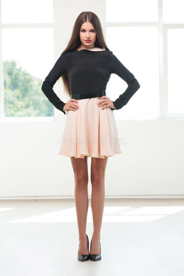 La jeune femme de mode tient des mains sur des hanches photographie stock