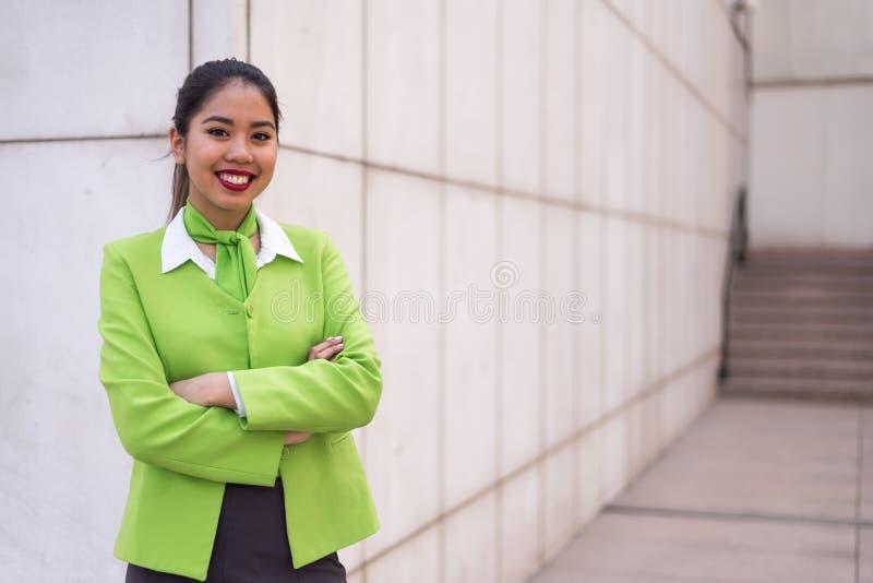 La jeune femme de scort ou les bras croisés de sourire d'équipage verdissent images libres de droits