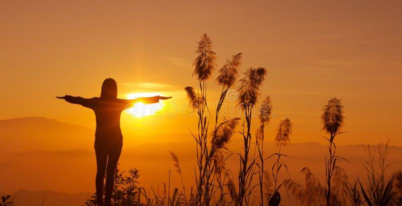 La jeune femme de silhouette de coucher du soleil se sentant à la liberté et détendent photographie stock libre de droits