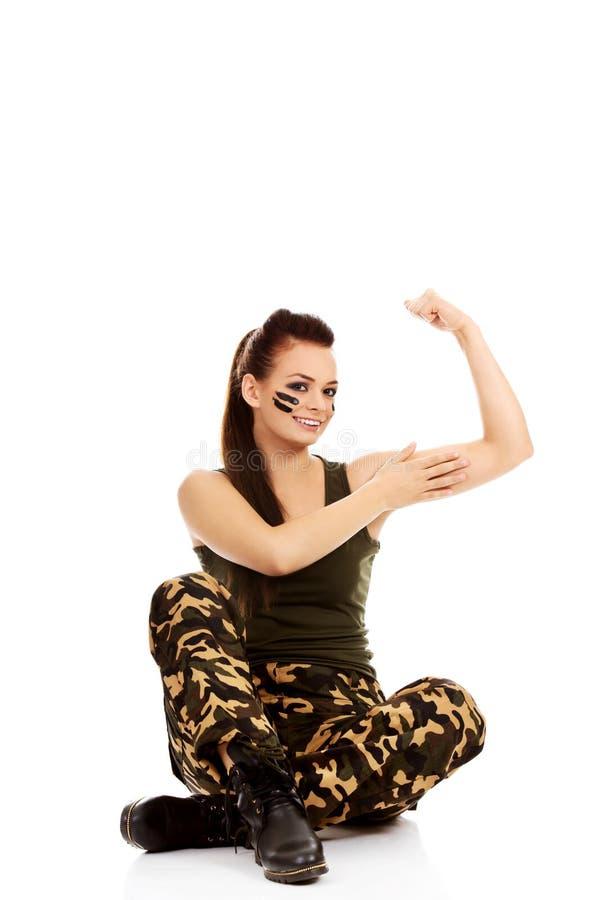 La jeune femme de soldat s'asseyant sur le plancher et lui montre des muscles images libres de droits