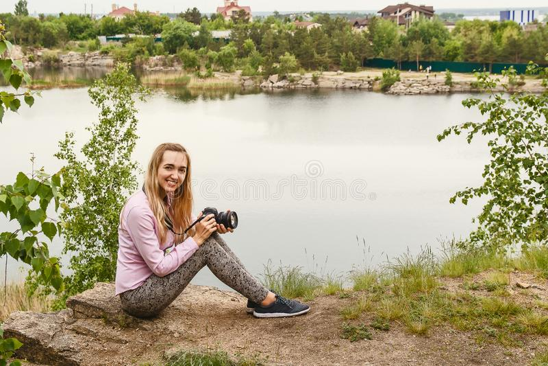 La jeune femme de sourire avec la cam?ra s'assied sur le rivage de lac images stock