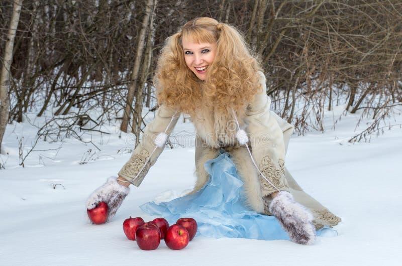 La jeune femme de sourire avec la coiffure exceptionnelle pose avec des pommes images stock