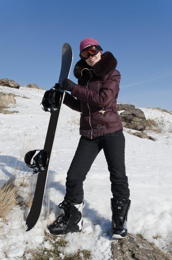 La jeune femme de sourire avec un snowboard images libres de droits