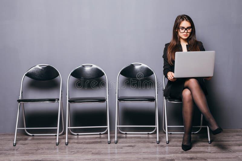 La jeune femme de sourire d'employé de bureau s'asseyant sur la chaise en bois de plancher utilisant l'ordinateur portable mobile photo stock