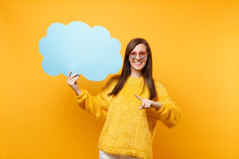 La jeune femme de sourire dans des lunettes de coeur dirigeant l'index sur le bleu vide vide disent le nuage, bulle de la parole  photo stock