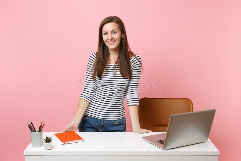 La jeune femme de sourire dans des vêtements sport travaillent, se tenant près du bureau blanc avec l'ordinateur portable contemp images stock