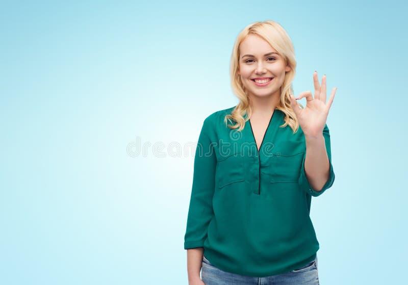 La jeune femme de sourire dans la chemise montrant la main correcte signent photo libre de droits