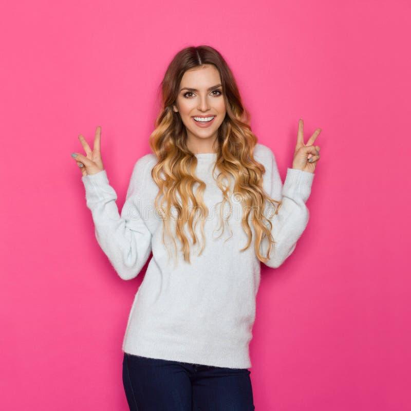 La jeune femme de sourire dans le chandail en pastel montre le signe de main de paix photo stock