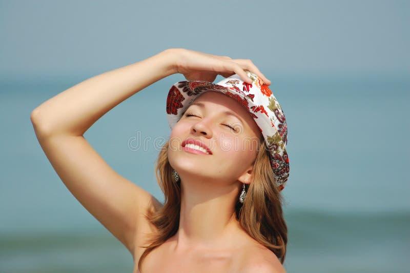 La jeune femme de sourire dans le chapeau avec les yeux étroits se bronze photos libres de droits