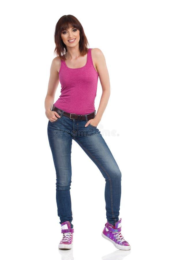 La jeune femme de sourire dans le dessus de réservoir rose se tient avec des mains dans des poches photographie stock libre de droits