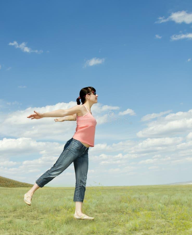 La jeune femme de sourire dans le domaine apprécient le soleil image libre de droits