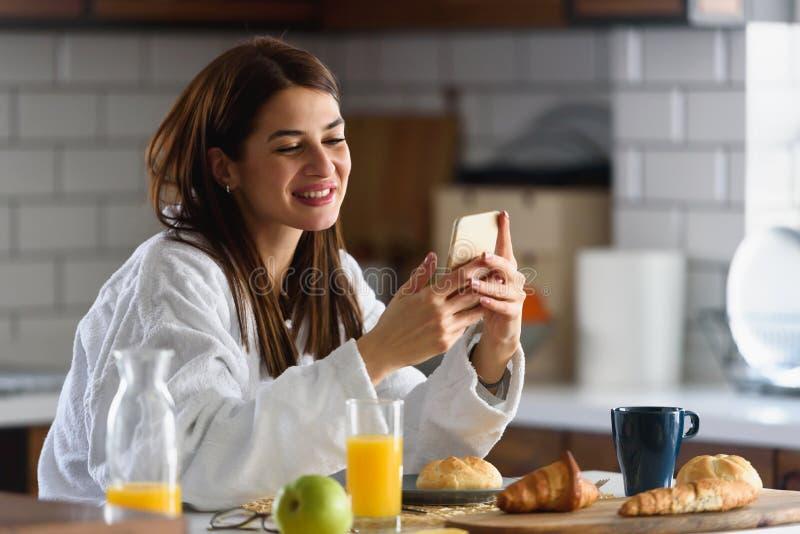 La jeune femme de sourire dans le peignoir s'est juste levée pendant le matin dans la cuisine utilisant le téléphone intellige photos libres de droits