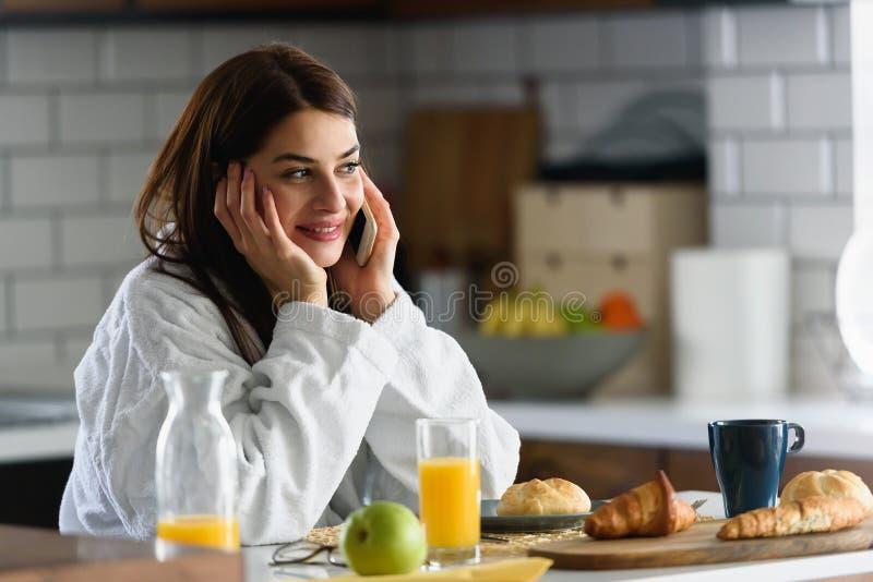 La jeune femme de sourire dans le peignoir s'est juste levée pendant le matin dans la cuisine utilisant le téléphone intellige photographie stock