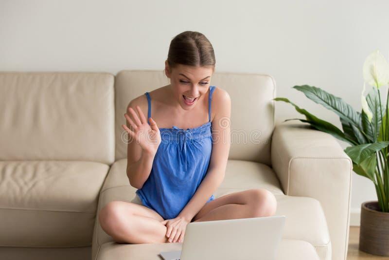 La jeune femme de sourire faisant la vidéo de distance invitent l'ordinateur portable, ondulant photos stock