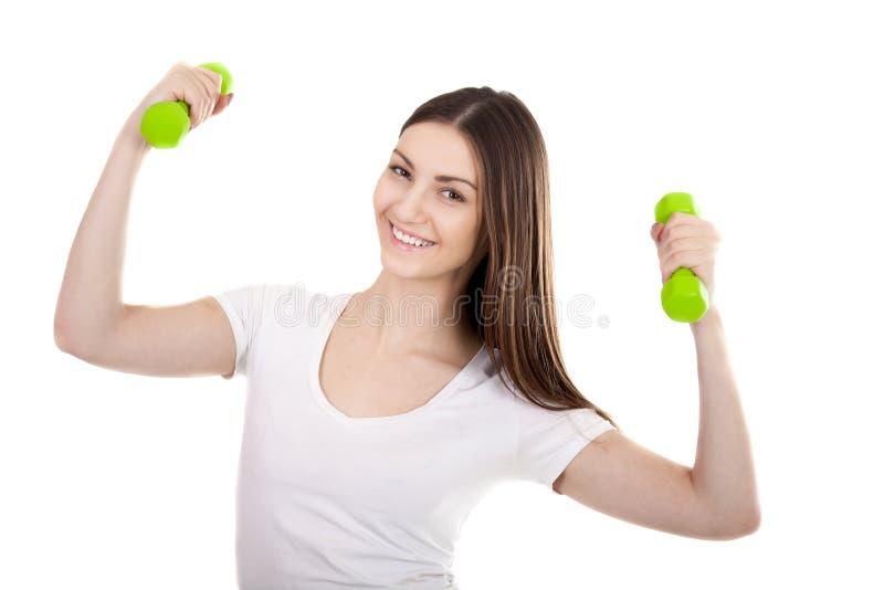 La jeune femme de sourire forme le biceps avec des haltères photographie stock libre de droits