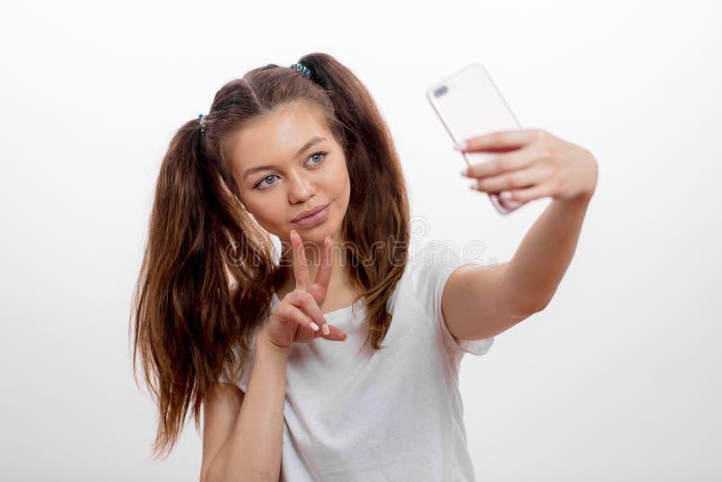La jeune femme de sourire a habillé montrer en passant deux doigts tout en prenant une photo images stock