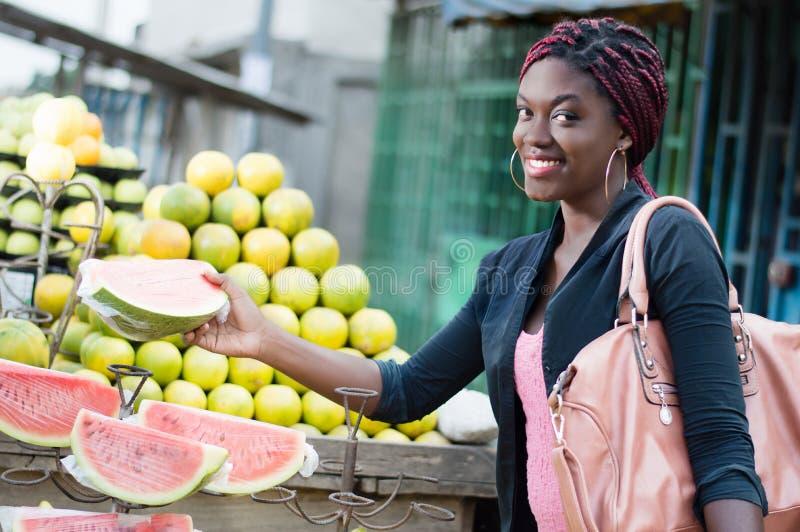 La jeune femme de sourire saisit une tranche de fruit mûr image stock