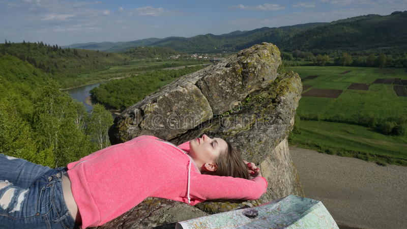 La jeune femme de touristes se trouvant sur les roches avec le voyage attribue : boussole, carte Fond de nature de source photo stock
