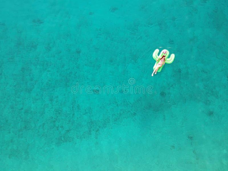 La jeune femme de vue aérienne sur le géant a gonflé le flotteur de cactus dans l'eau de turquois de la mer ionienne Albanie photo libre de droits