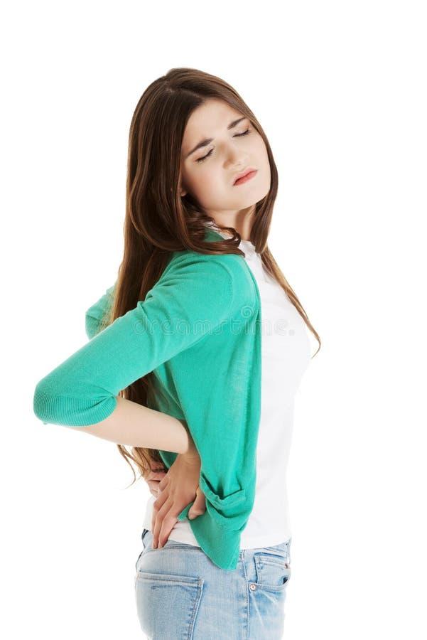 La jeune femme a des douleurs de dos. photos libres de droits
