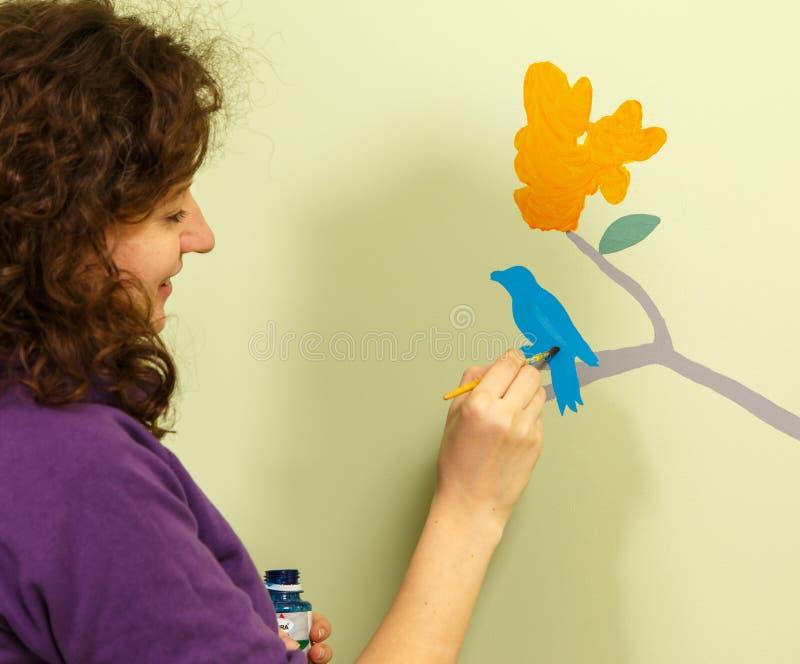 La jeune femme dessine l'oiseau et la fleur sur le mur image stock