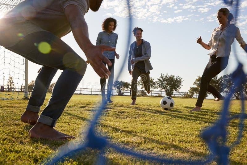 La jeune femme donne un coup de pied le football tout en jouant avec des amis images stock