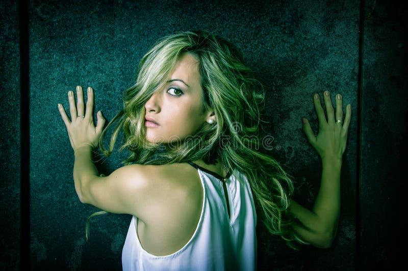 La jeune femme a effrayé avec ses mains au-dessus d'un métallique photos libres de droits