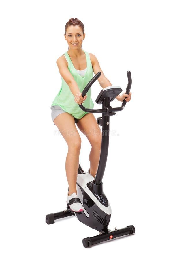 La jeune femme emploie l'entraîneur stationnaire de bicyclette. photo stock