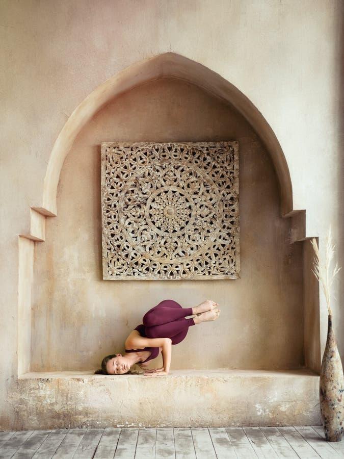 La jeune femme en costume de prune en pose de yoga image stock