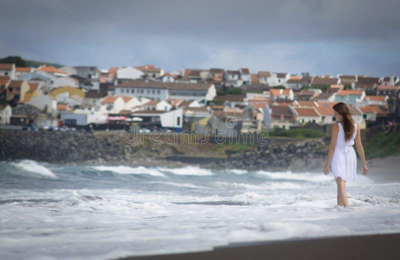 La jeune femme en mer de observation de robe blanche ondule sur la plage de Miguel de sao avec le sable voncanic noir, Açores image stock