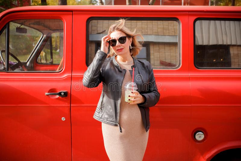 La jeune femme enceinte à la mode avec un sourire et une boisson à entrer dans des ses mains marche autour de la ville en été sur image stock
