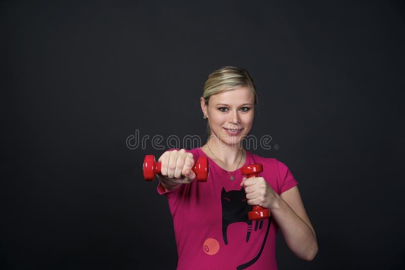 La jeune femme enceinte blondy dans le rose t-court avec le chat fait des exercices avec les haltères rouges de forme physique, f image libre de droits