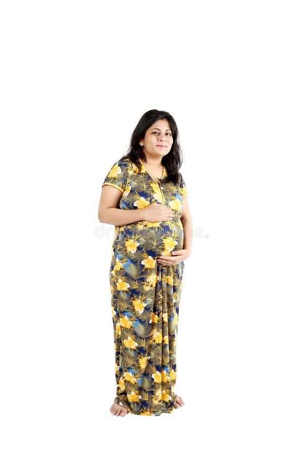 La jeune femme enceinte se tient avec le visage souriant photographie stock