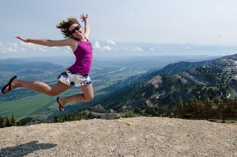 La jeune femme enthousiaste heureuse saute sur les montagnes grandes de Teton en Jackson Hole Wyoming pendant l'été Concept pour  photo libre de droits