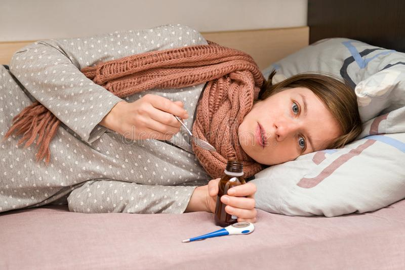 La jeune femme est malade Elle a attrapé froid, se sentant mal et prenant des médecines images stock