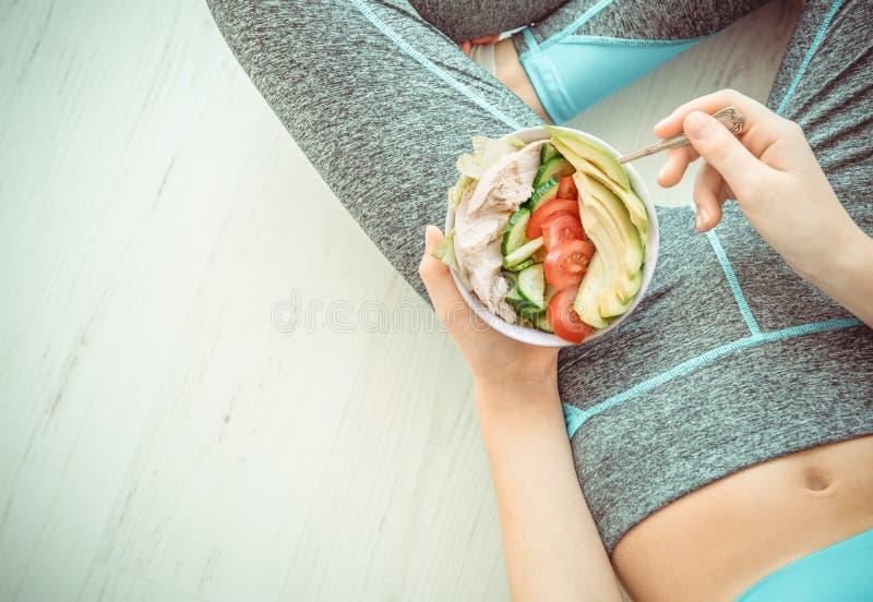 La jeune femme est reposante et mangeante d'une salade saine après une séance d'entraînement image libre de droits