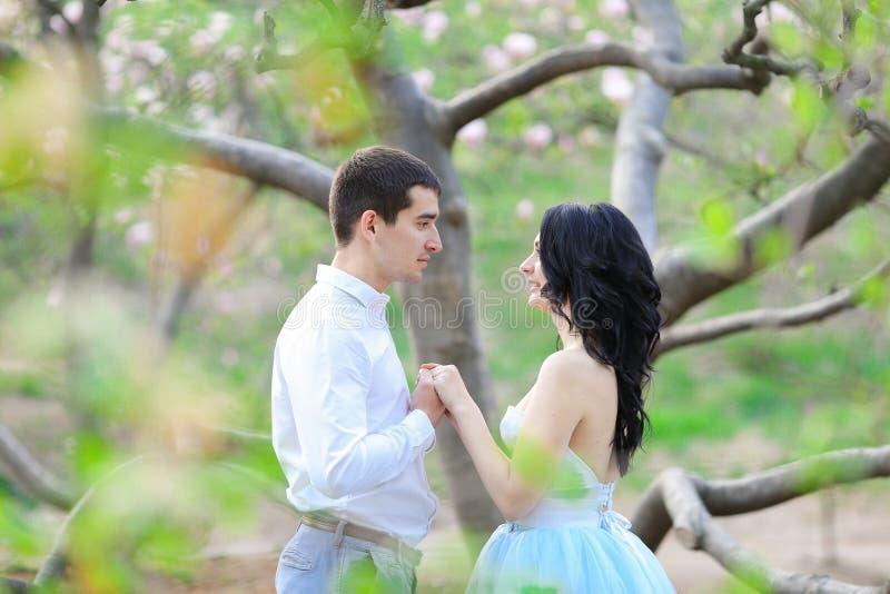 La jeune femme et la brune équipent étreindre près de l'arbre de floraison image stock