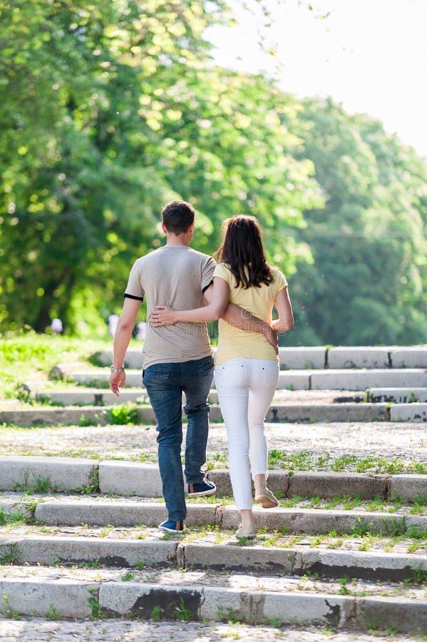 La jeune femme et l'homme de couples marchant dans la ville garent tenir des mains photo libre de droits
