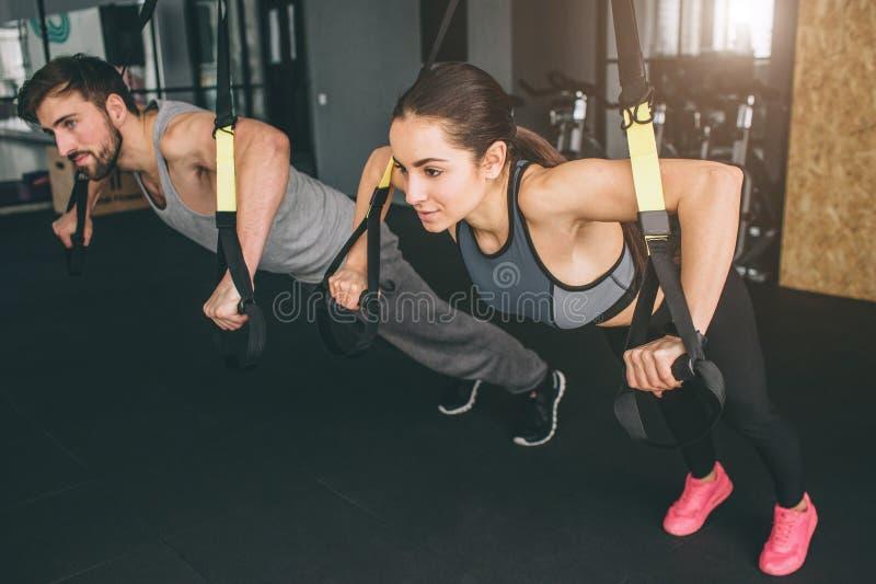 La jeune femme et l'homme font des exercices de presse de coffre de TRX Ils sont des associés de sport et faire tous les exercice images stock