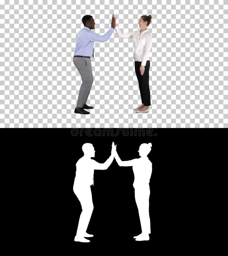 La jeune femme et le jeune homme dans des vêtements formels donnent haut cinq, Alpha Channel photo libre de droits