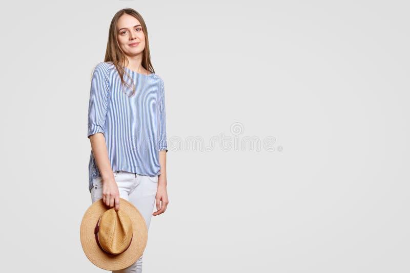 La jeune femme européenne décontractée attirante utilise le chemisier rayé à la mode, trouses blancs, le chapeau d'été de paille  photographie stock