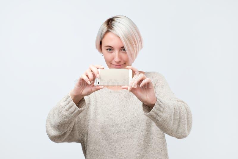 La jeune femme européenne dans le chandail fait la photo utilisant le téléphone image stock