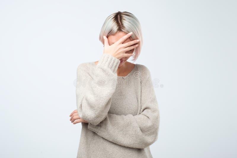La jeune femme européenne dans le chandail gris cache son visage, photo de studio d'isolement sur le fond gris image libre de droits