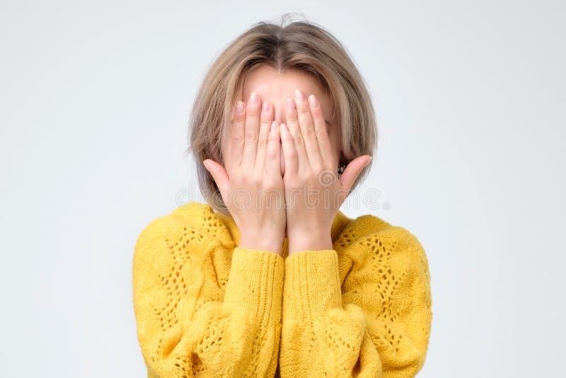 La jeune femme européenne dans le chandail jaune cache son visage image libre de droits